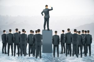 Businessman standing on pedestal and looking into the distance with other businesspeople around. Leadership concept